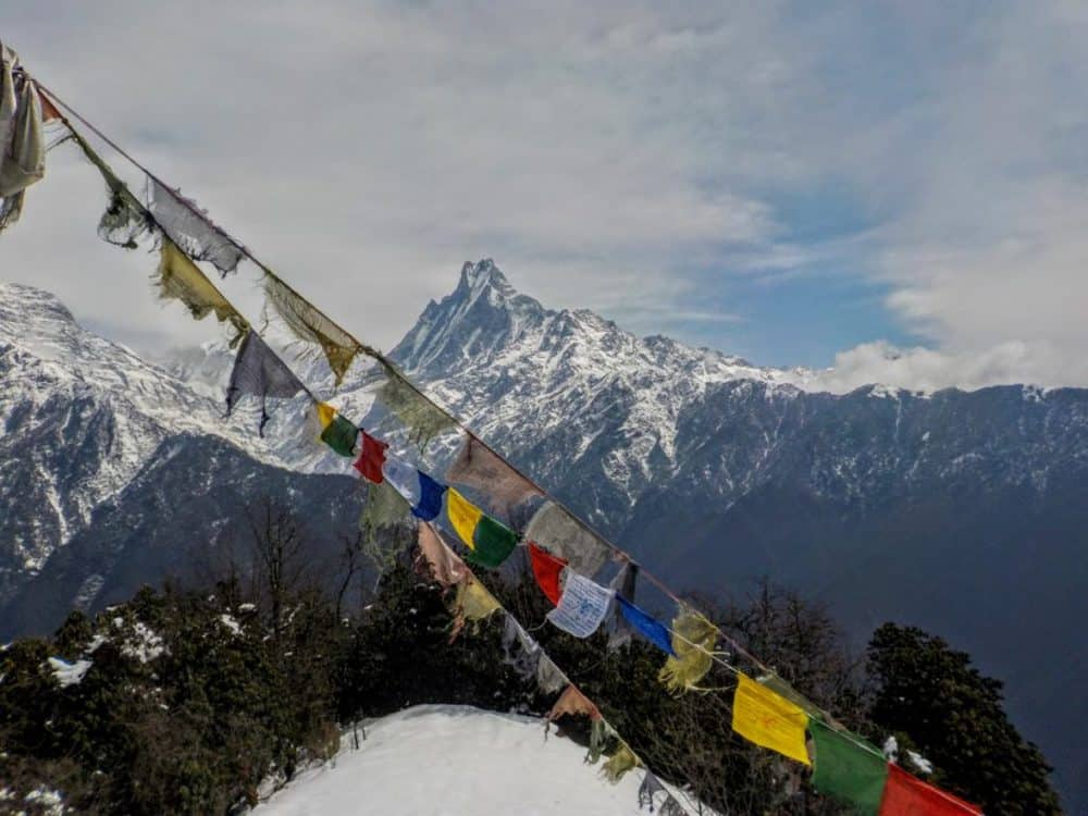 Buddhist prayer flags and a view of the jagged Machhapuchhre mountain in Nepal