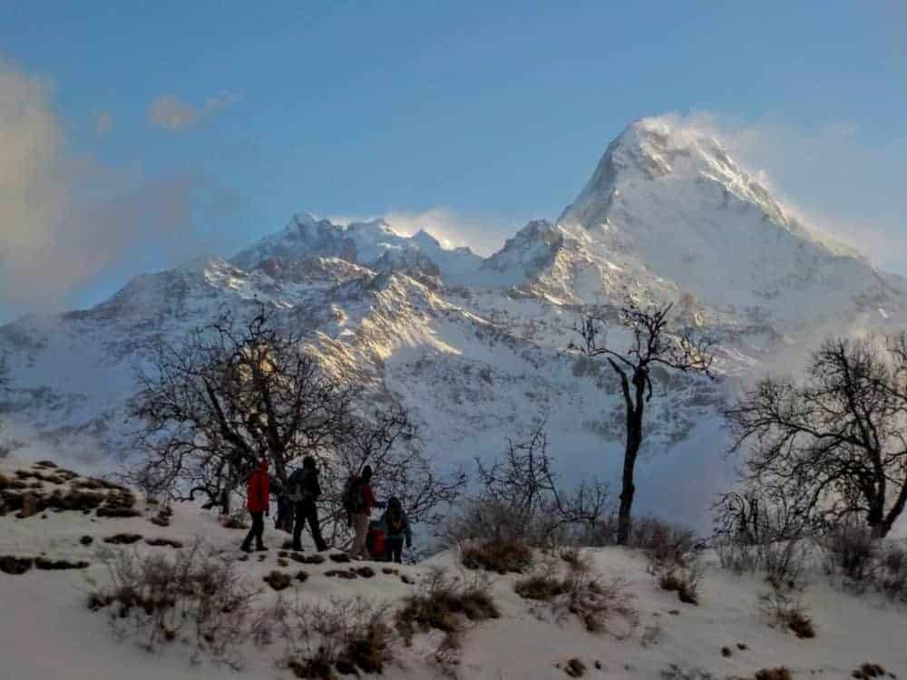 Hiking group overshadowed by the snow-covered Annapurna I.