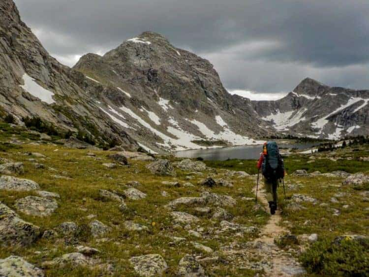 Hiker walking through a meadow surrounded by granite peaks