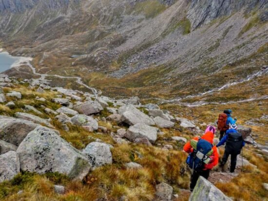 Hikers walking down a rocky slope toward a lake