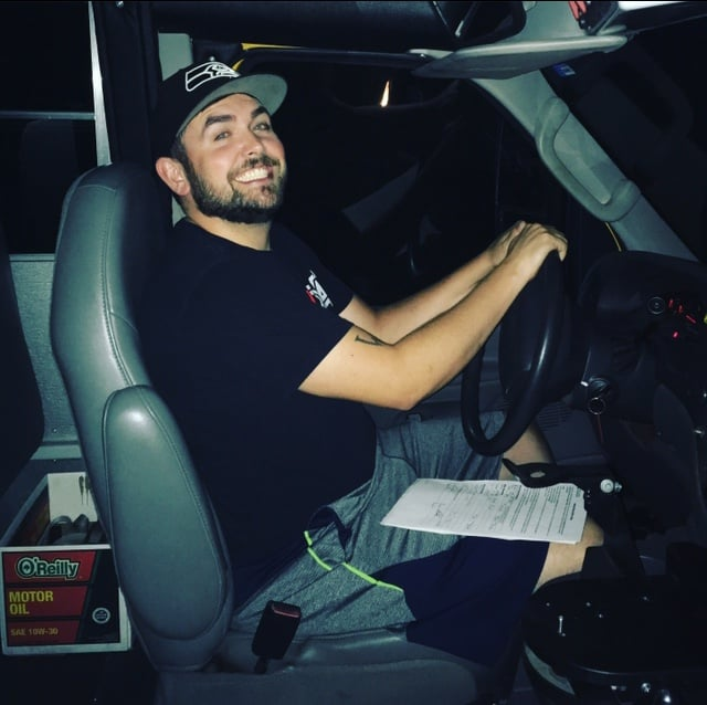 Aaron sits in the driver's seat of the bus.