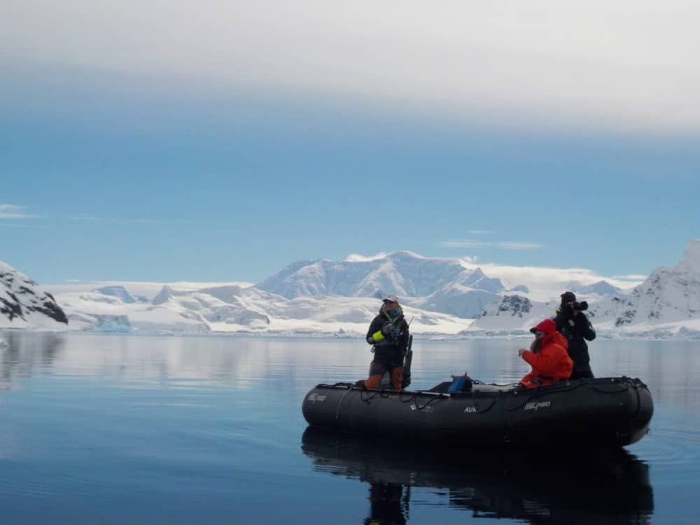 People on a black inflatable boat surrounded by snow covered mountains in Antarctica