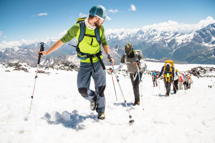 An outdoor adventure guide leads a group to the top of a snow-capped mountain