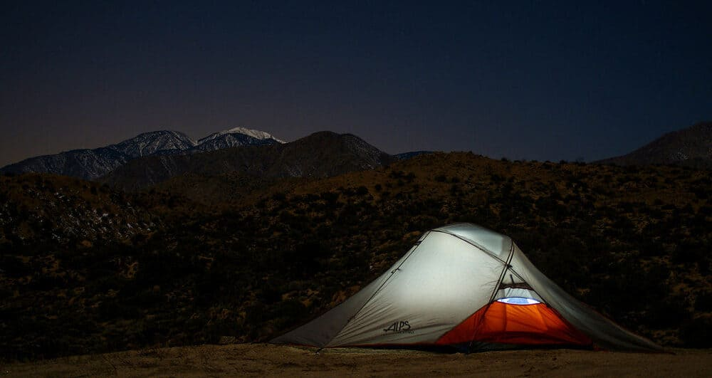 Red and white tent glows under a dark, starry night