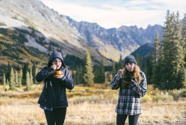 two girls eating backpacking food in the mountains