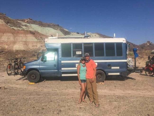 couple standing in front of their skoolie conversion