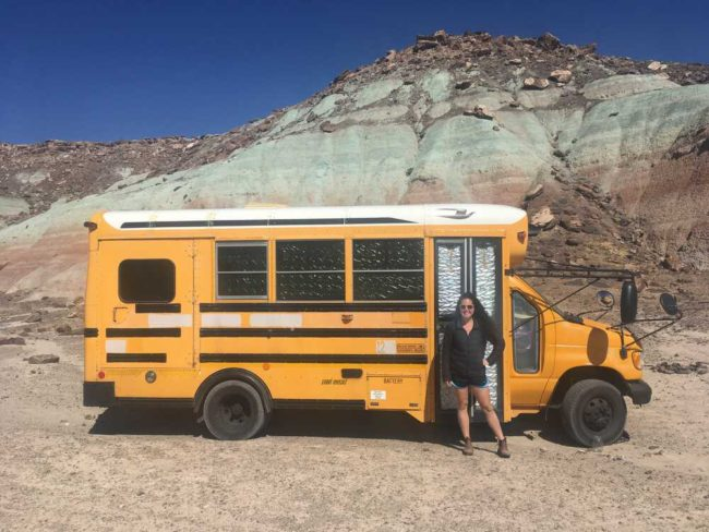 yellow school bus converted to an RV with owner standing out front