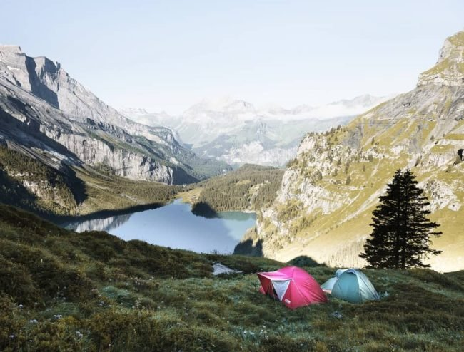 two colorful tents in alpine meadow above alpine lake with mountains to the side