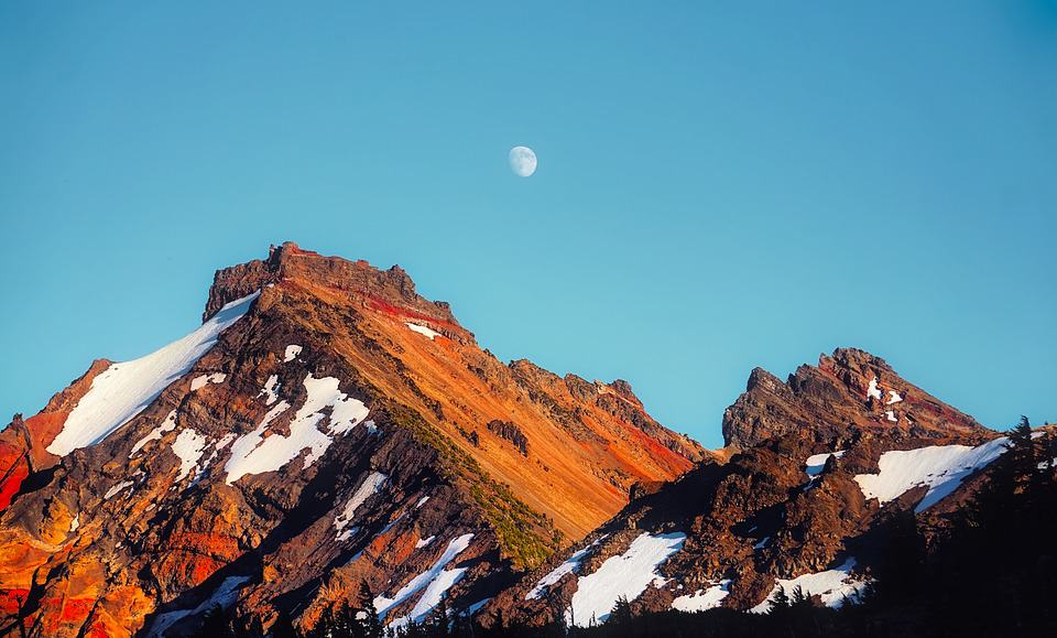 large snowy peak with moon in the background