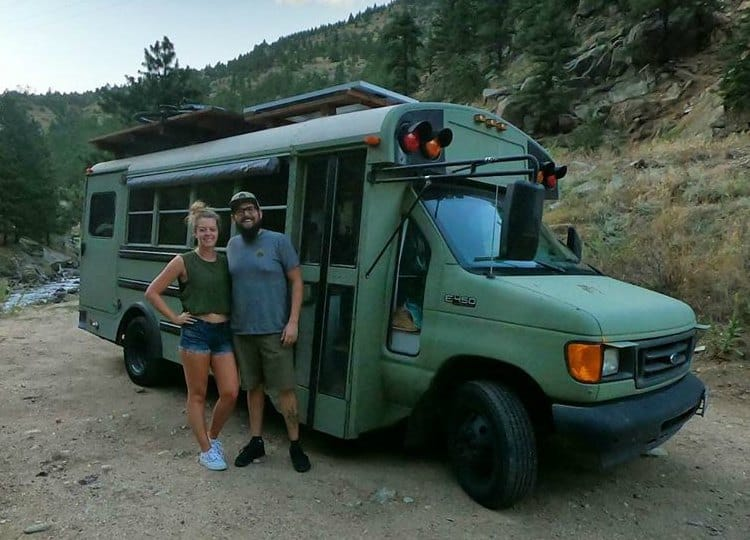couple standing in front of school bus conversion