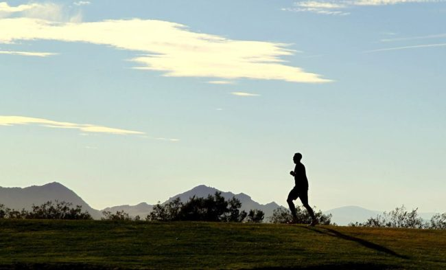 person wearing running shoes with mountains in the background