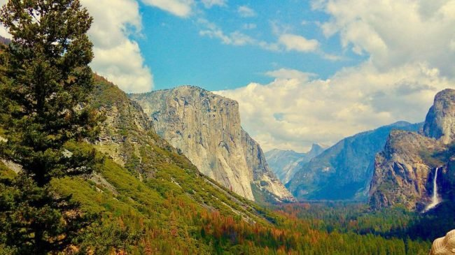 el capitan with half dome in the distance and fall foliage in the foreground