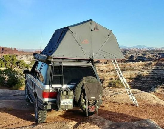 green tent on top of SUV with panoramic views of Utah desert in the background