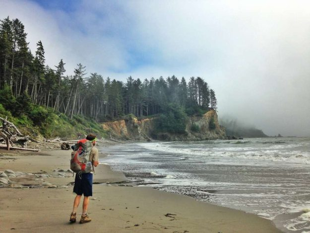 hiker standing on sandy beach in olympic national park