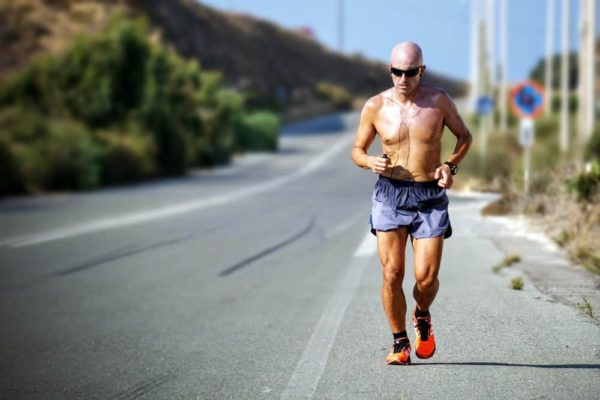 shirtless man running on road