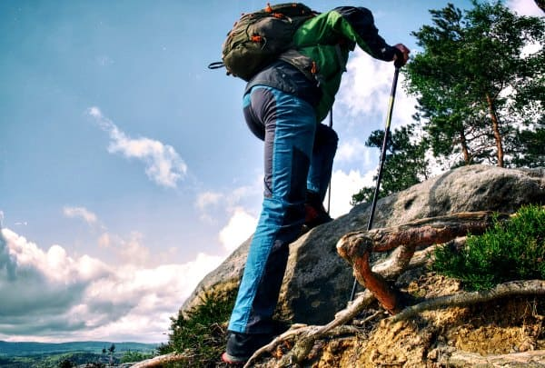 man using two trekking poles on steep terrain