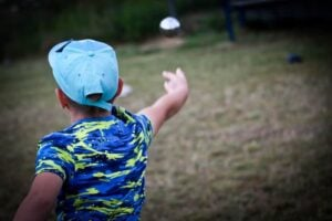 boy in blue hat throwing bocce ball