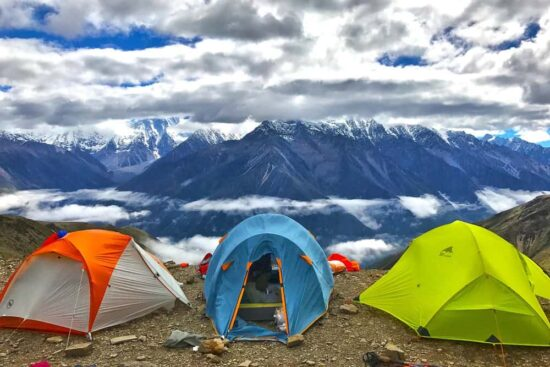 three colorful tents on a ridge with snow covered mountains in the background