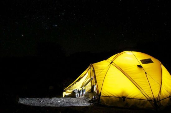 bright yellow tent illuminated against the black night sky