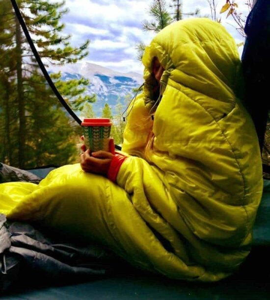 girl in yellow sleeping bag in tent