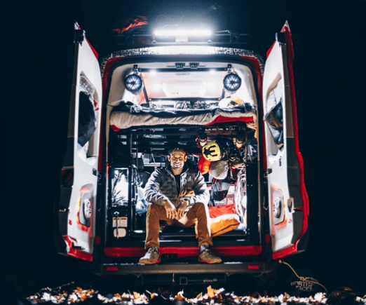 man sitting in back of customized red ford transit at night with headlamp