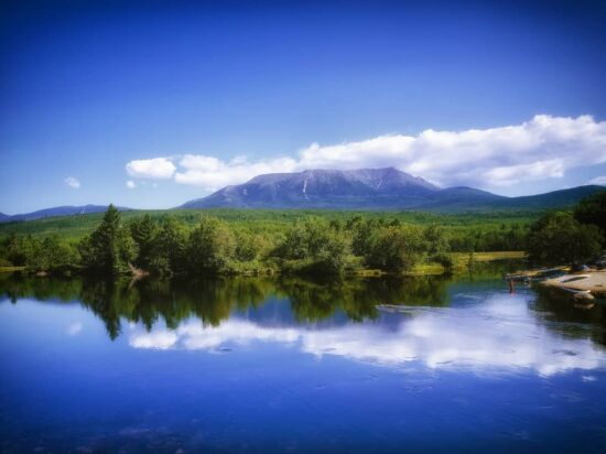 mount katahdin in the distance with blue sky and calm blue lake in the foreground