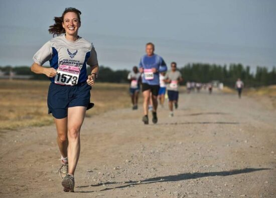 person running happily down a gravel road during a race
