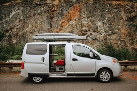 caravan outfitters white nissan van on the road