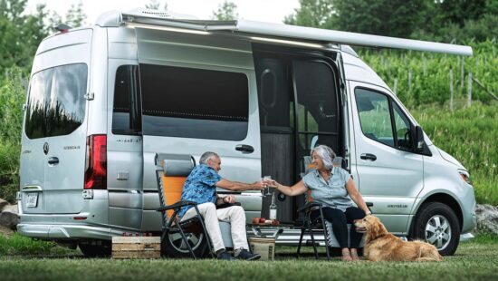 two people sitting outside airstream camper van with the power awning open