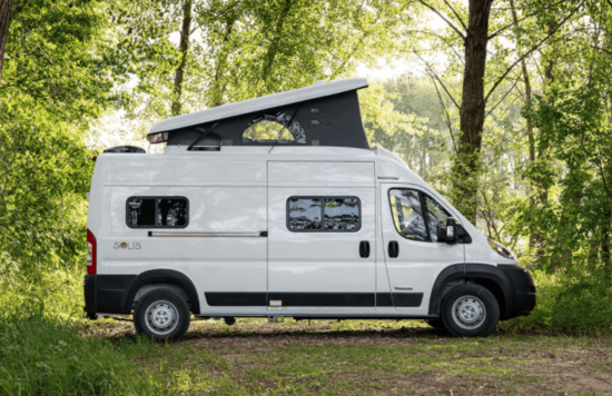 white winnebago solis with pop top in forest