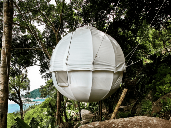 white sphere tree tent hanging in the woods