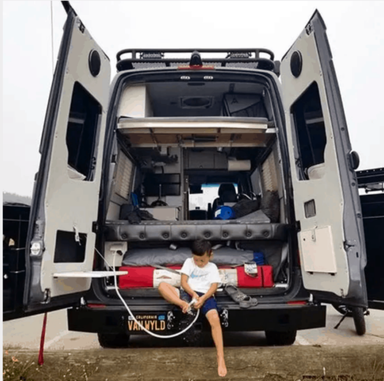 person sitting in the back of a converted van