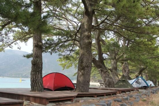red tent on a wooden platform by the lake