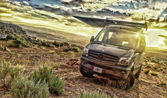 van driving on dirt road at sunset