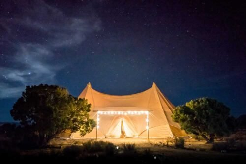 yellow tent illuminated in the starry sky