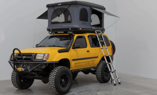 black hard shell rtt on top of a yellow truck