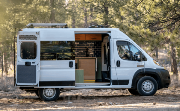 white converted promaster withe side door open in the woods