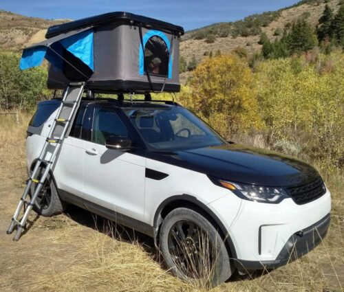 black and silver roof top tent on white and black suv