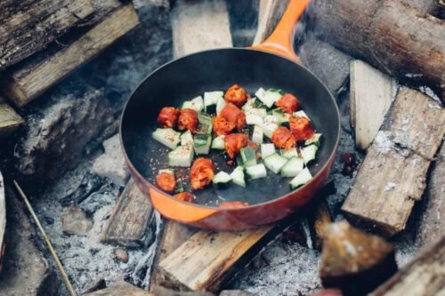 orange cast iron pan over the fire with vegetables grilling