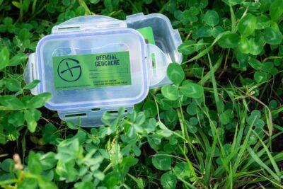 Small plastic geocache sitting in the green grass
