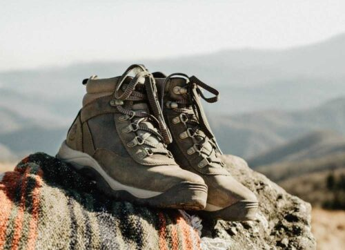 close up of hiking boots sitting on a rock with mountains in the background